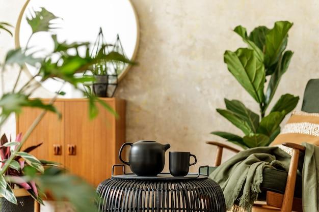 Stijlvolle compositie bij modern retro interieur met rotan salontafel, theepot, ronde spiegel, veel planten, fauteuil, lantaarn, commode, kussen, plaid en elegante persoonlijke accessoires in woondecoratie.