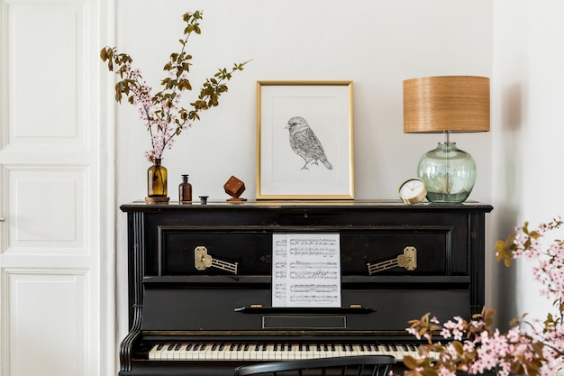 Stijlvolle compositie bij woonkamer interieur met zwarte piano, gouden posterframe, gedroogde bloemen, gouden klok, designlamp en elegante persoonlijke accessoires in modern interieur.