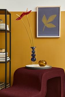 Stijlvolle compositie in modern woonkamerinterieur met designkruk, vaas met bloem, boekenkast en frame. gele muur..