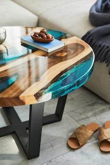 Stijlvolle compositie met design epoxy salontafel, bank, deken, kussens, boek, decoratie en persoonlijke accessoires in modern interieur. details.