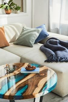 Stijlvolle compositie met design epoxy salontafel, bank, deken, kussens, boek, decoratie en persoonlijke accessoires in modern interieur.. details.