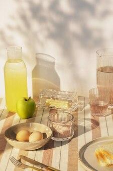 Stijlvolle compositie van buitenkeukenruimte met houten tafel, eten, drinken, keukenaccessoires, beige tafelkleed en zomerschaduwen. landelijke sfeer..
