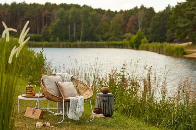 Stijlvolle compositie van buitentuin aan het meer met design rotan fauteuil, salontafel, plaid, kussens, drankjes en elegante accessoires.