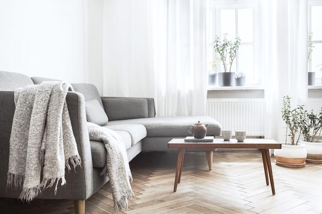 Stijlvolle compositie van creatief ruim woonkamerinterieur met bank, salontafel, planten, tapijt en accessoires. witte muren en parketvloer.
