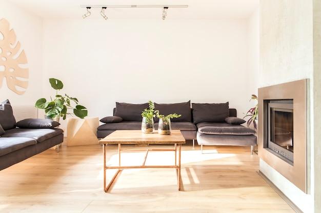 Stijlvolle compositie van creatief ruim woonkamerinterieur met banken, fauteuil, salontafel, planten, open haard en accessoires. neutrale muren.