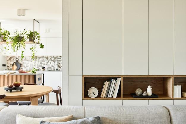 Stijlvolle compositie van creatieve woonkamer interieurdetails zoals boeken, klokken en andere persoonlijke accessoires. witte panelen. keuken op de achtergrond.