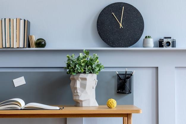 Stijlvolle compositie van een thuisbureau met boeken, kantoorbenodigdheden, fotocamera, cactussen, houten lambrisering met plank en elegante persoonlijke accessoires in een modern interieur.