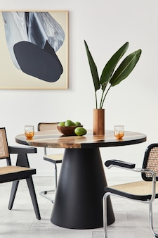 Stijlvolle compositie van eetkamerinterieur met designtafel, moderne stoelen, decoratie, tropisch blad in vaas, fruit, abstracte schilderijen en elegante accessoires in woondecoratie.
