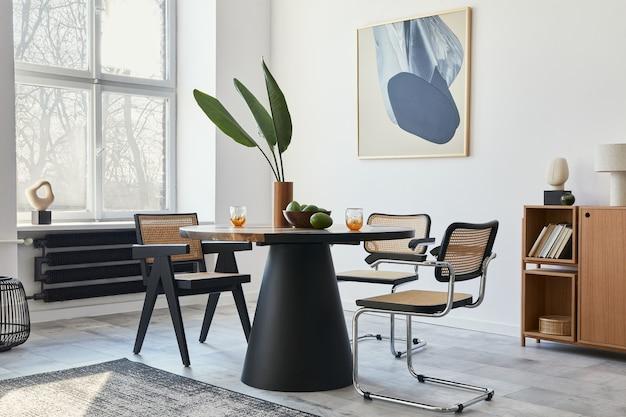 Stijlvolle compositie van eetkamerinterieur met designtafel, moderne stoelen, decoratie, tropisch blad in vaas, fruit, boekenkast, abstracte schilderijen en elegante accessoires in woondecoratie.