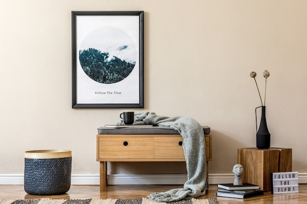 Stijlvolle compositie van gezellig en modern hal interieur met frame houten commode plaid plant en accessoires beige muur parketvloer