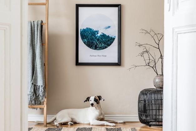 Stijlvolle compositie van gezellig en modern hal/woonkamer interieur met frame, houten commode, plaid, plant, hond en boho accessoires. beige muren, parketvloer.