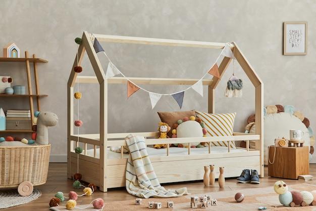 Stijlvolle compositie van gezellig scandinavisch kinderkamerinterieur met houten bed, plank, pluche en houten speelgoed en hangende textieldecoraties. neutrale creatieve muur, tapijt op de vloer. sjabloon.