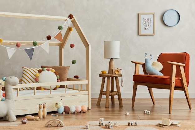 Stijlvolle compositie van gezellig scandinavisch kinderkamerinterieur met houten bed, rode fauteuil, pluche en houten speelgoed en hangende decoraties van textiel. creatieve muur, tapijt op de vloer. sjabloon.