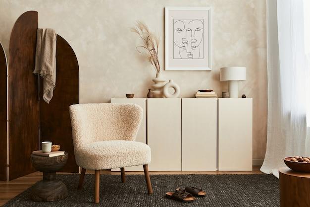 Stijlvolle compositie van gezellig woonkamerinterieur met mock-up posterframe, pluizige fauteuil, kamerscherm, salontafel, commode en persoonlijke accessoires. moderne stijl. sjabloon.