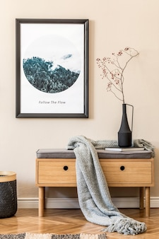 Stijlvolle compositie van gezellige en moderne hal interieur met frame houten commode plaid plant en accessoires beige muren parketvloer