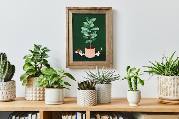 Stijlvolle compositie van huistuininterieur met mock-up posterframe, gevuld met veel mooie planten, cactussen, vetplanten, luchtplant in verschillende designpotten. huis tuinieren concept. sjabloon.