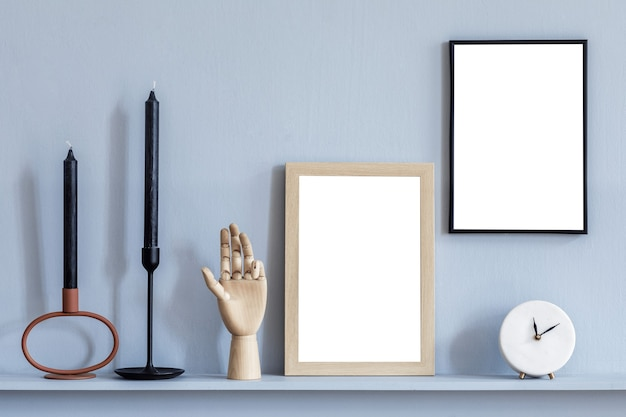 Stijlvolle compositie van kamerinterieur met twee mock-up posterframes en zwarte kaarsen