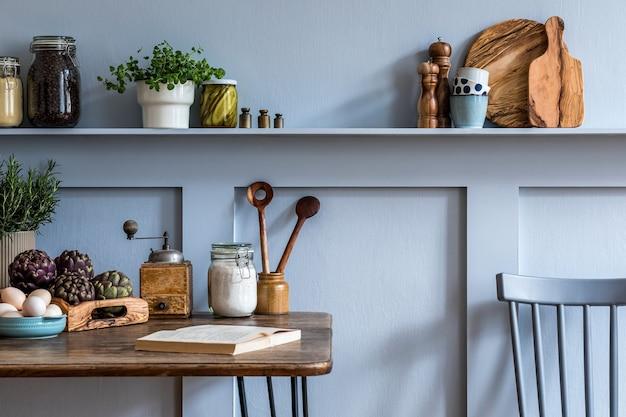 Stijlvolle compositie van keukeninterieur met houten familietafel, stoelen, groenten, kruiden, planten, fruit, voedselvoorraden en keukenaccessoires in grijs concept van woondecoratie.