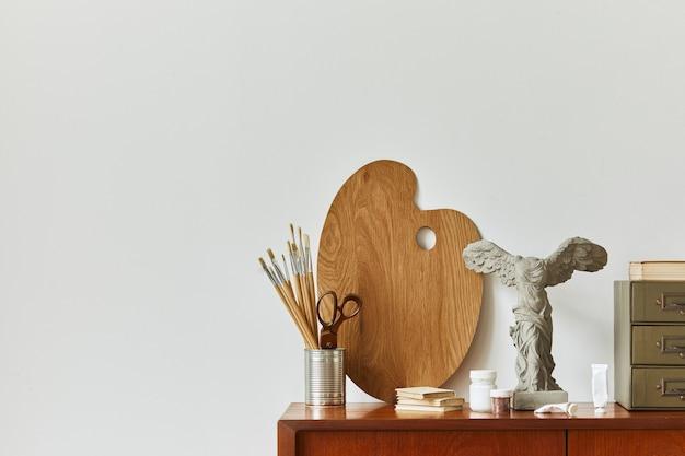 Stijlvolle compositie van kunstenaarswerkruimte met design retro teakhouten commode, posterlijst, boek, decoratie en schilderaccessoires.