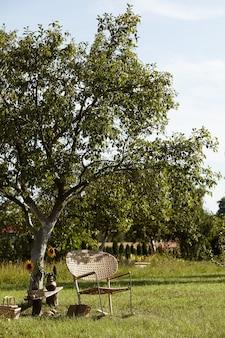 Stijlvolle compositie van landelijke tuin met design rotan fauteuil, houten bank, plaid, eten, drinken en elegante accessoires. veel kleurrijke bloemen. zomerstemming.