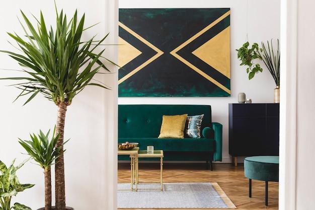 Stijlvolle compositie van modern ruim appartement interieur met groene bank salontafel planten tapijt en mooie accessoires witte muren en parketvloer zwart groene en gouden kleuren