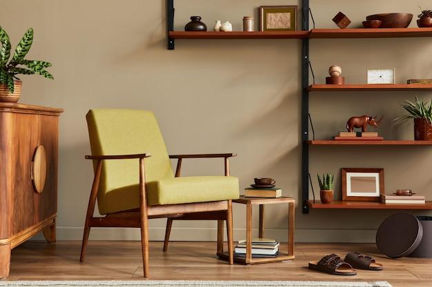 Stijlvolle compositie van retro woonkamer interieur met design fauteuil, houten boekenkast, fotolijsten, plant, tapijt, slippers, decoratie en elegante accessoires in woondecoratie.