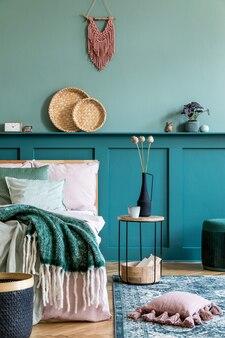 Stijlvolle compositie van slaapkamerinterieur met houten bed, designmeubels, plank, bloemen in vaas en elegante persoonlijke accessoires. mooie lakens, deken en kussen. home enscenering.