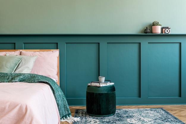 Stijlvolle compositie van slaapkamerinterieur met houten bed, designmeubels, plank, fluwelen poef en elegante persoonlijke accessoires. mooie lakens, deken en kussen. . thuis enscenering.