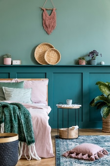 Stijlvolle compositie van slaapkamerinterieur met houten bed, designmeubels, plank, planten, decor en elegante persoonlijke accessoires. mooie lakens, deken en kussen. . thuis enscenering.