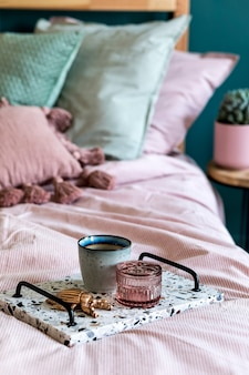 Stijlvolle compositie van slaapkamerinterieur met lastrico-dienblad met koffie en elegante persoonlijke accessoires. mooie roze en groene lakens, deken en kussen. ontwerp thuisopvoering. detailopname