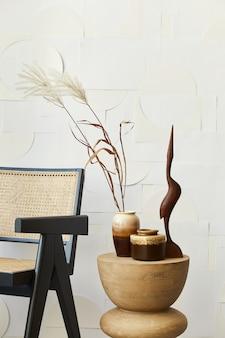 Stijlvolle compositie van wit woonkamerinterieur met designstoel, beige houten kruk, gedroogde bloemen in vaas en kunstschilderijen aan de muur.