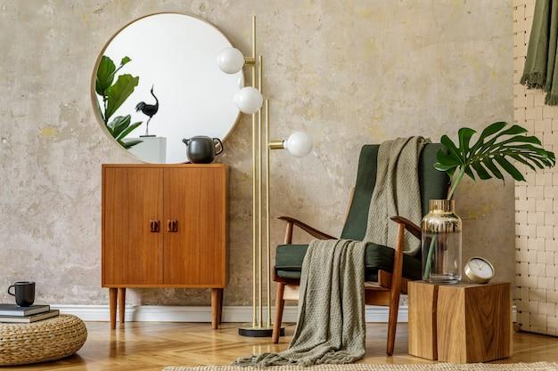 Stijlvolle compositie van woonkamer interieur met design fauteuil, lamp, rotan poef, commode, tropische bladeren, plaid, tapijt, spiegel en elegante persoonlijke accessoires in modern retro concept.