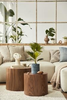 Stijlvolle compositie van woonkamer met design beige bank, houten kruk, cactussen, planten, boek, decoratie, meubels en elegante persoonlijke accessoires. moderne woondecoratie. open ruimte. sjabloon.