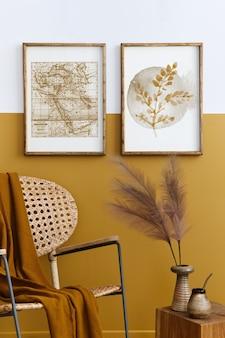Stijlvolle compositie van woonkamerinterieur met design rotan fauteuil, twee posterframes, planten, kubus, palid en persoonlijke accessoires in honinggeel woondecor