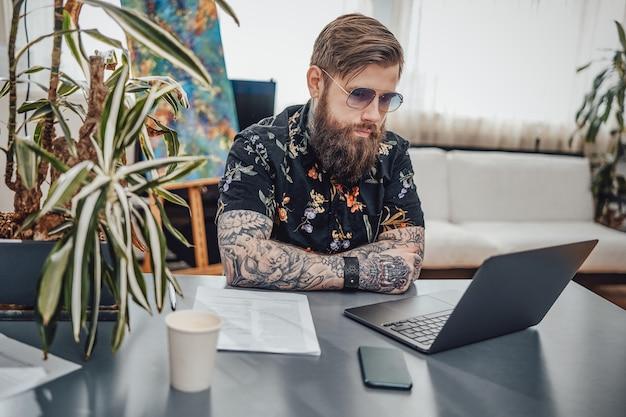 Stijlvolle computerprogrammeur met tatoeages werkt thuis op een laptop. professioneel portret van een hipstermens en zijn werk op afstand.