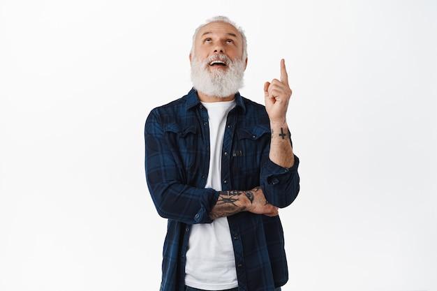 Stijlvolle coole grootvader met tatoeages en lange baard, kijkend en wijzende vinger omhoog naar advertentie, starend naar promotionele tekst copyspace, staande over witte muur