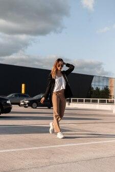 Stijlvolle coole vrouw in modieuze vrijetijdskleding uit nieuwe collectie in trendy zonnebrillen in witte sneakers loopt op asfalt op zonnige dag. aantrekkelijk modern meisjesmodel loopt parkeerplaats in de buurt van winkel