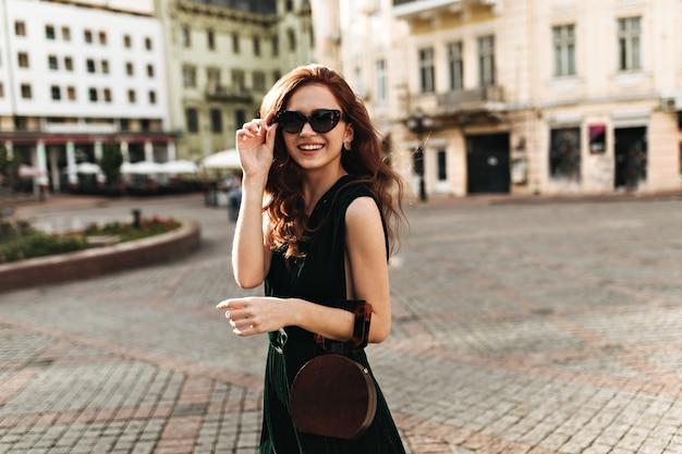 Stijlvolle dame die in zonnebril door stad loopt