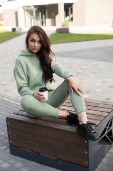 Stijlvolle dame die sportkleding en sneakers draagt en tijd doorbrengt in de stad terwijl ze geniet van een warm drankje. vrouwelijke mode. stadslevensstijl