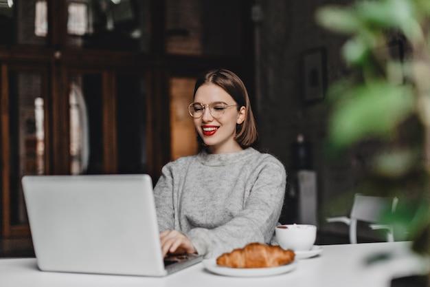 Stijlvolle dame in glazen en kasjmier trui met glimlach werken in grijze laptop, zittend in café met croissant en kopje koffie op tafel.