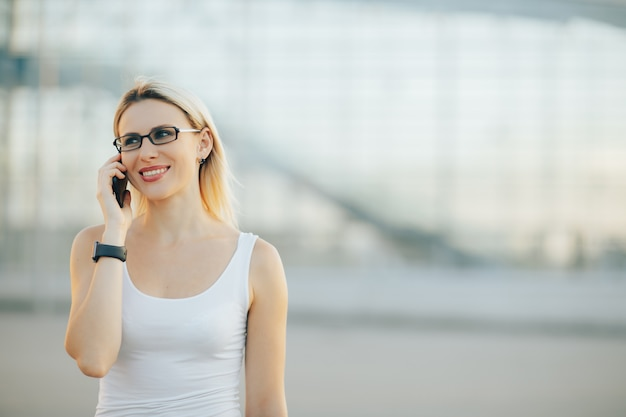 Stijlvolle dame in glazen praten aan de telefoon en glimlachen