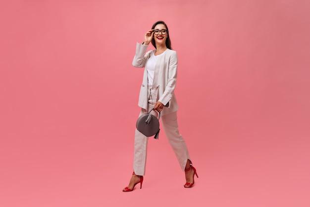 Stijlvolle dame in pak houdt handtas en loopt op roze achtergrond. zakenvrouw met donker haar met felrode lippen en stijlvolle hakken glimlachen.