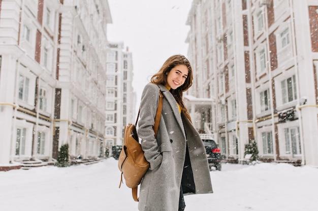 Stijlvolle dame met bruine rugzak die door de stad loopt onder sneeuwval. buiten foto van mooie vrouw met charmante glimlach poseren in grijze jas op stedelijke scène
