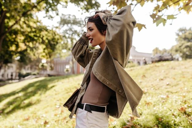 Stijlvolle dame met brunette kort kapsel in spijkerjasje vormt buitenshuis. koele vrouw die in witte jeans weg naar buiten kijkt.