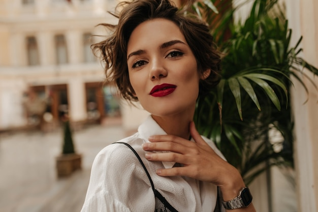 Stijlvolle dame met kort kapsel in licht overhemd glimlachend in café. donkerbruine vrouw met rode lippenstift in restaurant.