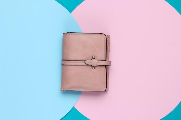Stijlvolle dames lederen portemonnee op achtergrond met blauw roze pastel cirkel. creatief minimalistisch modestilleven. bovenaanzicht