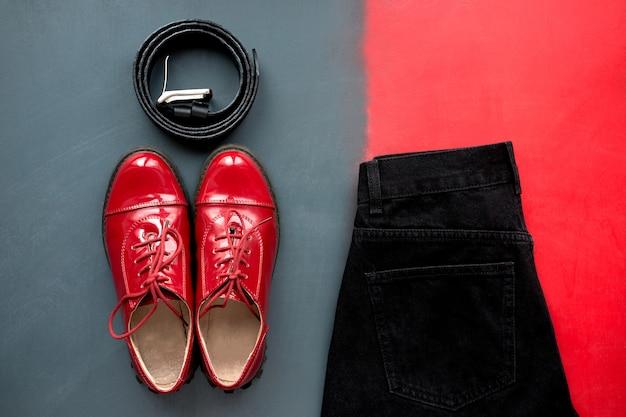 Stijlvolle dameskleding. set van modieuze zwarte leren riem, stijlvolle rode lakleren schoenen en klassieke zwarte jeans op grijze en rode achtergrond. bovenaanzicht.