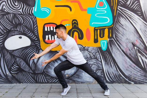 Stijlvolle danser tegen graffiti muur