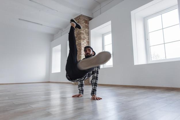 Stijlvolle danseres man met een pet in casual kleding breakdance dansen in de hal
