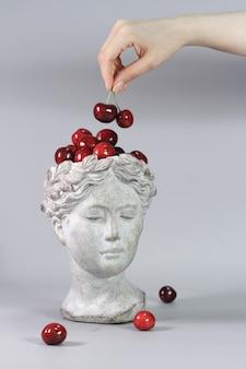 Stijlvolle decoratie gemaakt in de vorm van een grieks godinnenhoofd vol rode rijpe kersen. mooie designelementen.
